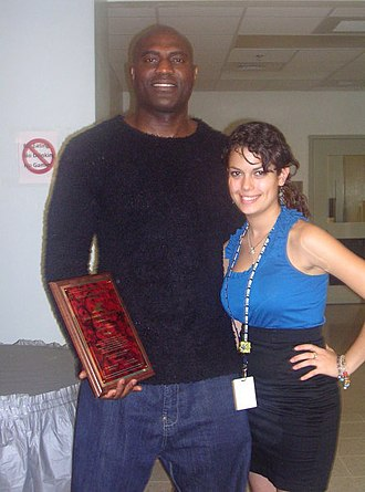 Dave Thomas (cornerback) - Dave Thomas with a student at Miami Beach Senior High holding his Beach High Hall of Fame plaque