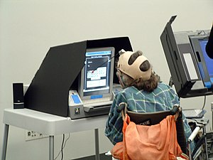 Assistive technology - This voter with a manual dexterity disability is making choices on a touchscreen with a head dauber