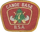 Patch with a red background and a gold border; the text Canoe Base BSA in the border; in the center a silver canoe superimposed with crossed paddles, a green pine tree and the number 7 in gold