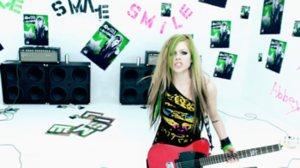 """Smile (Avril Lavigne song) - Lavigne performing """"Smile"""" in a white room. The walls are plastered with posters and spray painted words."""