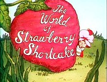 "A six-year-old girl, dressed in a pinafore and wearing a pink dust cap on top of her hair, looks out to the right of a giant strawberry.  On the strawberry, the words ""The World of Strawberry Shortcake"" are written in cursive."