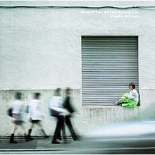A woman sitting on a ledge at the bottom of a concrete garage building while motion-blurred school children walk past