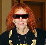 The head and shoulders of a man with ginger hair, wearing sunglasses, a neckless, and a dark jacket with gold trim over the top of a dark T-shirt.