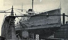 A large ship in a drydock, surrounded by construction equipment.