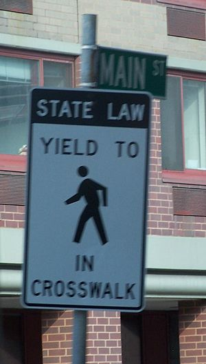 A NY-standard yield-to-peds sign on Roosevelt ...
