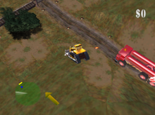 An industrial field with dirty grass and patches of dirt. A bulldozer is centered in the screenshot, traveling to the upper left towards railroad tracks and a bush. Nearby are lights along a road, both lit and unlit. Close behind is a red fire engine-like vehicle with two cylinders mounted atop, along its length. In the bottom left of the heads up display is a green radar circle showing obstacles in the upper left, and alongside the radar, a yellow arrow pointing to the upper left, indicating the location of the next structure in the red carrier truck's path. In the upper right of the heads up display is the number zero, preceded by a dollar sign, indicating that no damage to property has been scored.