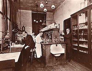 Charles Norris (medical examiner) - Charles Norris (seated, left) and Alexander Gettler (far right) in the toxicology laboratory located on the third floor of the City Morgue, Bellevue Hospital c.1922