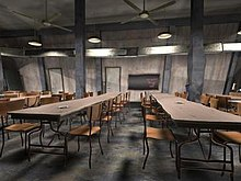 A grey wall with two doors is in the background, a chalkboard in its centre, and ceiling fans and hanging lights are overhead. In the foreground are two long cafeteria tables extending into the background, each having ten chairs; other tables are partially visible to the left and right.