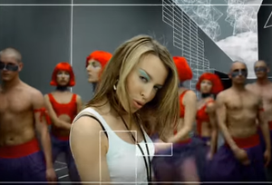 "Love at First Sight (Kylie Minogue song) - Still from the music video ""Love at First Sight"", showing Minogue dancing in a digitalized maze with back-up dancers."