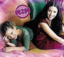 Two young teen girls on a purple couch, one lying prone and one sitting. Both are smiling.