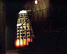 In a dark basement, a white Dalek (see previous description) appears to levitate up a small staircase of approximately seven stairs. The body of the Dalek is white, with shiny gold vertical slats and gold balls on its lower half. There is an orange-yellow glow at the Dalek's base.