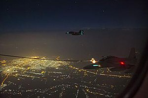 Two Royal Australian Air Force Super Hornet aircraft conduct air to air refuelling with a RAAF Multi Role Tanker Transport aircraft by night over the skies of Iraq.jpg