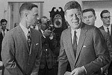 Black-and-white film screenshot showing the main character on the left looking towards another man, President Kennedy, (voiced by actor Jed Gillin), on the right. Kennedy is smiling and looking to his left. In the background several men are looking in different directions and one is aiming a camera.