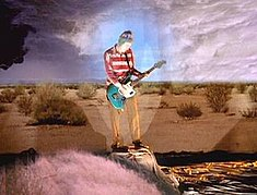 Frusciante Standing On A Pedestal With Inverted Superimposed Images Behind Him In The Music Video For Under The Bridge