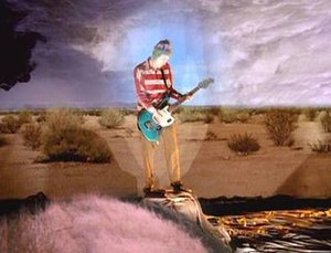 "Under the Bridge - Frusciante standing on a pedestal with inverted superimposed images behind him in the music video for ""Under the Bridge"""