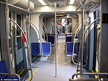 Interior of a light rail vehicle with blue seats, gray walls and silver pedestrian supports.