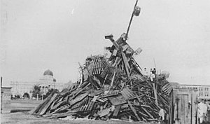 Aggie Bonfire - The Aggie Bonfire as it appeared in 1928 on the Drill Field in front of the Academic Building (in background)