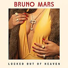 "A key in between a woman's breasts, she also has several rings in her fingers and her finger nails painted in red. The word ""Locked Out of Heaven"" with capital font can be seen on the bottom of the picture, while the words ""Bruno Mars"" in red capital font are on the top of the image."