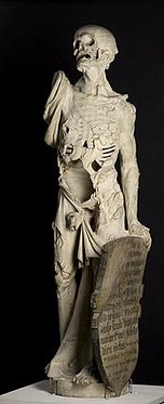 Statue showing Death as a living skeleton. His right arm is missing and he looks upwards, while holding a shield with his right. The shield contains rows of inscriptions.