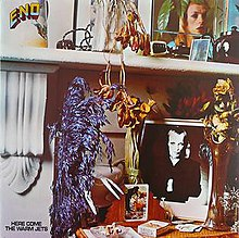 "A close up photo of a mantle with a desk below it. Items on the mantle include a color photo of Brian Eno, a kettle and flowers. Items on the desk below are a black-and-white photo of Eno, flowers, playing cards and cigarettes. In the top left corner of the album cover ""Eno"" is written. At the bottom left corner of the album, ""Here Come the Warm Jets"" is written."
