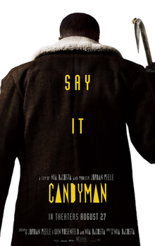 """The Candyman faces opposite the viewer. On top of his large dark coat are the words """"Say It"""" and """"Candyman"""" in yellow font."""