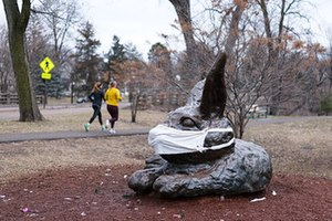 Een bronzen beeld van een konijn liggend op zijn kant op een bed van rode mulch.  De oren staan rechtop en een stoffen masker bedekt zijn neus en mond.  Daarachter is een bruin gazon, een voetpad waarop twee joggers lopen, een parkway en loofbomen die net beginnen te bladeren.