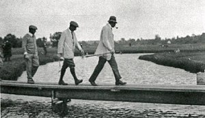 Percy Barrett (golfer) - George Cumming (far left), Harry Vardon (middle), and Ted Ray (front) walking across a bridge at Lambton Golf and Country Club, Toronto, Ontario, in a 1913 exhibition golf match. Barrett (not pictured) partnered with Cumming.