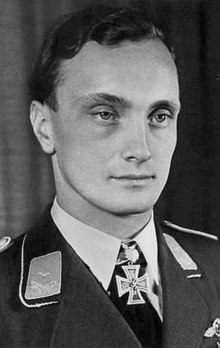 A young man with slightly curly hair wearing a military uniform and an Iron Cross shaped military decoration at his neck.
