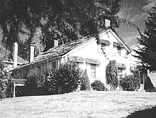 A modest two-story farmhouse with a peaked roof and four chimneys sits under a large tree at the top of a sloping lawn. Bushes and shrubs grow near the house on its two visible sides. A small part of a neighboring house, perhaps only 15 feet (4.6 m) away, can be seen in the background.