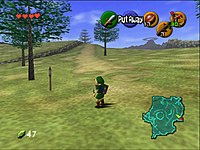 The child version of the game's protagonist, Link, stands in Hyrule field wearing his distinctive green tunic and pointed cap. In each corner of the screen are icons that display information to the player. In the upper left-hand corner there are hearts, which represent Link's health, in the lower left-hand corner is a counter that displays the quantity of Rupees (the in-game currency) possessed by the player. There is a mini-map in the lower right-hand corner, and five icons in the upper right-hand corner, one green, one red, and three yellow, which represent the actions available to the player on the corresponding buttons of the N64 controller.