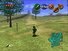 The child version of the game's protagonist, Link, stands in Hyrule field wearing his distinctive green tunic and pointed cap. In each corner of the screen are icons that display information to the player. In the upper left-hand corner there are hearts which represent Link's health, in the lower left-hand corner is a counter which displays the quantity of Rupees (the in-game currency) possessed by the player. There is a mini-map in the lower right-hand corner, and five icons in the upper right-hand corner, one green, one red, and three yellow, which represent the actions available to the player on the corresponding buttons of the N64 controller.