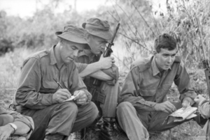 A soldier holding a map is talking while two other soldiers sitting nearby look on while taking notes.