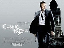 "A man in a business suit with a loose tie holding a gun. Behind him is a silhouette of a woman showing a building with a sign reading ""Casino Royale"" and a dark grey car below the building. At the bottom left of the image is the title ""Casino Royale"" – both ""O""s stand above each other, and below them is a 7 with a trigger and gun barrel – and the credits."