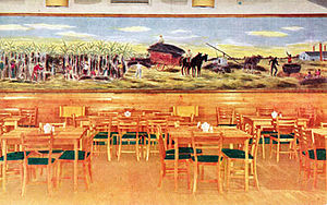 "Keesler Air Force Base -  Officers' Club at Keesler Field as it appeared during World War II. ""Partial view of the Dining Room, Officers' Club, Keesler Field, Mississippi. The mural scene, painted by Cpl. Claude Marks, shows the harvesting and processing of cane sugar in Louisiana around 1859.""  Source: U. S. Government postcard. Date of postcard unknown, probably about 1944."