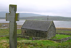 small stone chapel with cross overlooking a loch