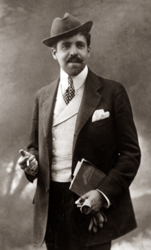 photograph of elegantly dressed white man with neat moustache and beard, wearing a hat at a jaunty angle; he has a cigarette in his right hand