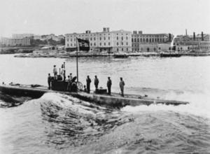 Un submarino emergido avanza con su tripulación de pie en la cubierta y en la torre de mando.  La ciudad de Pola se puede ver al fondo y la insignia naval de Austria-Hungría vuela desde la torre de mando del submarino.  La escotilla de entrada principal del barco está abierta con un submarinista parado a mitad de camino dentro.