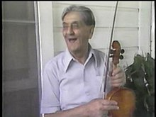 An image of Dennis McGee holding his violin during an interview with PBS's American Patchwork.