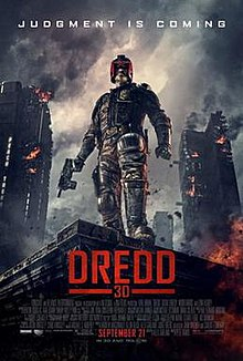 A futuristic police officer in armour and a helmet that covers all but his mouth stands on the corner of a building roof with a gun in his hand as large tower blocks burn behind him. Above the man reads a tagline