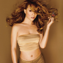 Image shows Carey standing in front of a brown/gold background in a beige sleeveless and mid-baring top, with darker matching pants. Her hair is long and golden-auburn, and is flowing in the air. Carey's left hand is touching the flowing tips of her hair and has a jeweled belt along her navel.