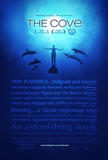 "A man swimming underwater surrounded by five dolphins. Above is the title ""The Cove"" and the tagline ""Shallow Water, Deep Secret"". Below is a group of quotes from film critics giving praise to the film, with the credits of the film at the bottom."
