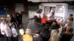 A white ice cream van is parked on a car park in front of a building. A man in a visor and a white jacket is hanging out of a side window of the van, and is handing a glowing object to a young girl in a red jumper and black skirt. Twenty-three similarly-aged children stand in a horseshoe shape around the girl.