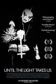 film title, awards and critical commentary imposed over a stark black-and-white image of a man in black metal-wear – black clothing, spikes and corpse paint – holding an inverted cross