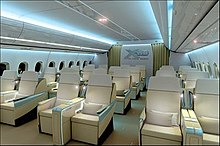 Mock-up of aircraft cabin with white seats, indirect lighting and a bluish hue