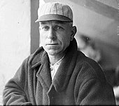 Black and white image of Hugh Duffy in a baseball cap and jacket, facing left