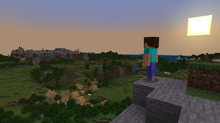 The default player skin, Steve, stands on a cliffside overlooking a village in a forest. In the distance, there is a small mountain range. The sun is setting to the right, making the sky turn pink and blue.