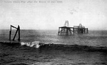 A black-and-white image of the pier after being destroyed by a storm. The deck and the chains are missing, and the nearest platform has been removed apart from a few broken piles.