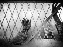 A black and white image of the film depicting the village doctor's hands and arms above flour as he presses up against a chain link fence.