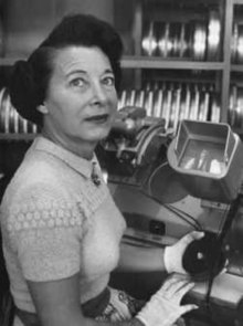 Photograph of the head and torso of a woman. She is seated in front of a Moviola machine. She is wearing white cloth gloves and is holding a reel of film. A rack with additional reels of film is visible in the background.
