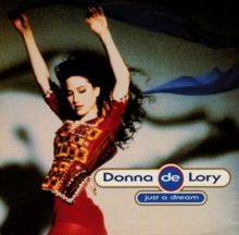 Donna de Lory wearing a red patterned dress with her arms above her head. The single name is written beside her image.